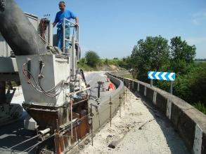 Ouvrier en train de mettre en place le long d'une route une bordure coulée grâce à une machine