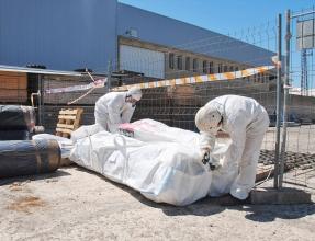 Ouvriers en train d'emballer des éléments amiantés